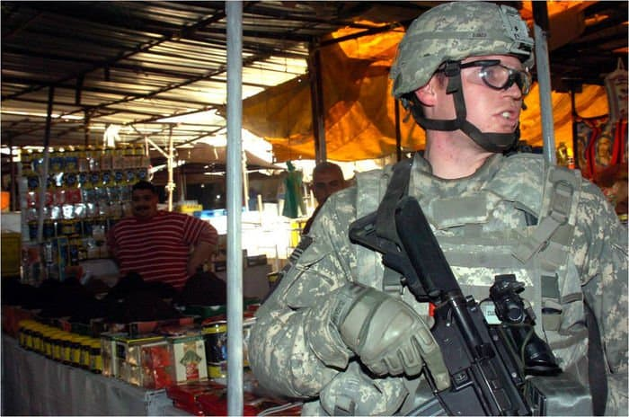 Staff Sgt. Jeremy Danmeyer scans a crowd of shoppers as his patrol moves through a market in central Baghdad.