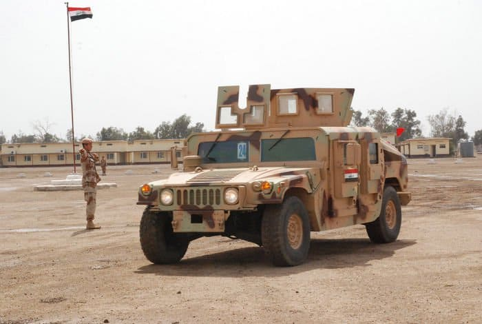 Two Iraqi Soldiers drive off in an M1114 humvee transferred from the U.S. Army to the Iraqi Security Forces