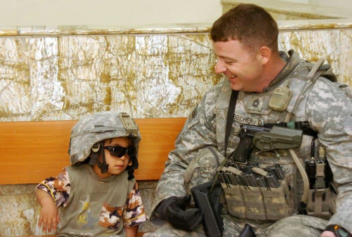 Sgt. 1st Class James Boucher gives an Iraqi child an opportunity to dress up as a U.S. Army Soldier at the Al Fahdl Clinic.