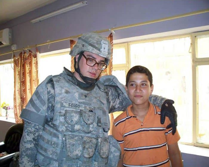 Spc. Michael Toigo, an artilleryman from Merrillville, Ind., 10th Mountain Division, takes time to talk with an Iraqi boy in a neighborhood school while patrolling in the Riyadh area of Baghdad.