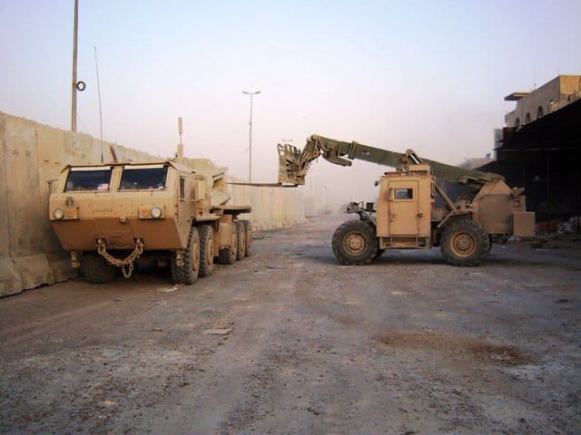 Soldiers unload a T-wall barrier with a Skytrak forklift on Al Quds street in Sadr City.