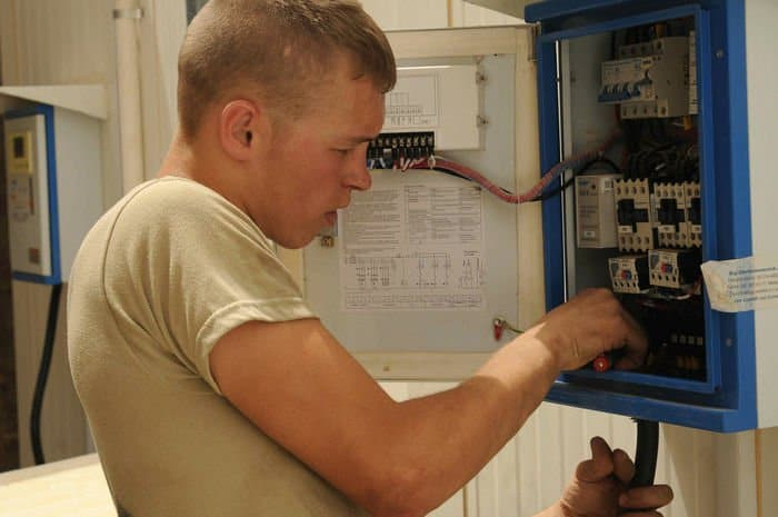 Private First Class Daniel Lodermeier installs a fuse box for the C Housing Unit at Joint Security Station Sadr City.
