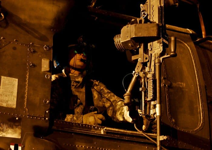 Sgt. David Brocato, crew chief, mans the gunner seat of a Blackhawk helicopter before the start of a mission on Camp Taji