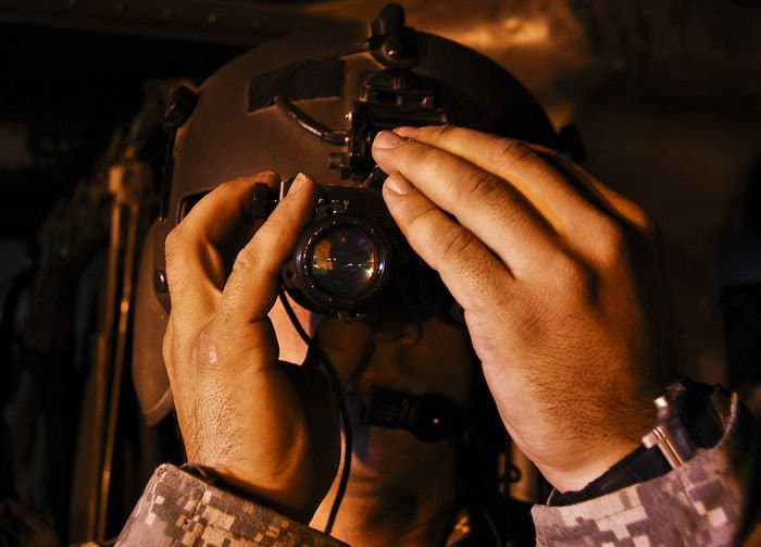 Sgt. David Brocato focuses his night vision goggles before a late night mission at Camp Taji