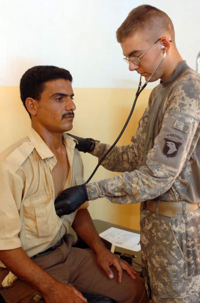 Spc. Benjamin Ulery checks a Sons of Iraq, or Abnaa al Iraq heart beat at a medical screening in Radwaniyah.
