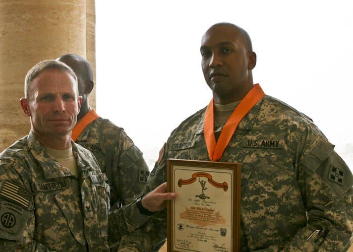 Col. Campbell Cantelou, Multi National Corps communications chief,presents the Bronze Order of Mercury award to 1st Sgt. Eric Crayton