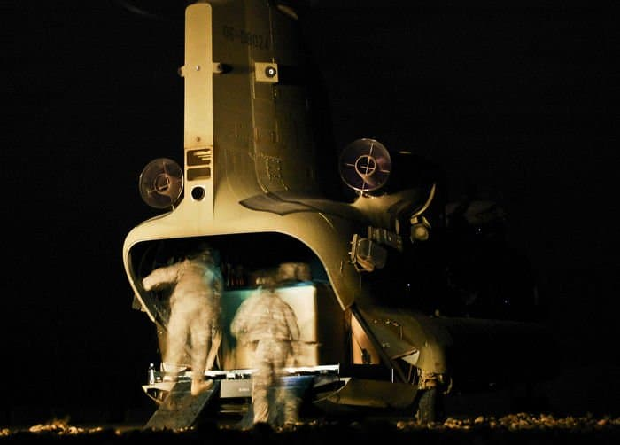 Company B soldiers load cargo into the back of a CH 47F Chinook Improved Cargo helicopter for a late night mission.