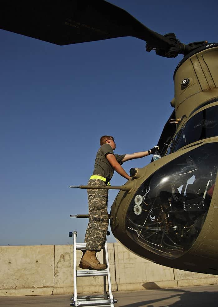 Pfc. Daniel Halweg cleans a CH 47F Chinook windshield in pre flight inspection.