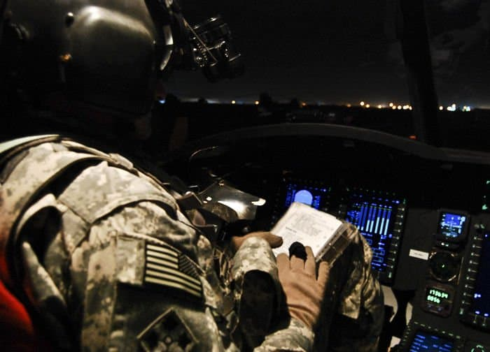 CH 47F Chinook pilot, Chief Warrant Officer 2 Jeremy Vance looks over his late night mission flight checklist.