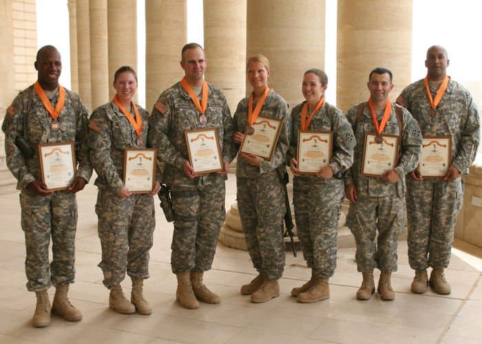 Seven Soldiers of Company C, Division Special Troops Battalion, 4ID, pose with their plaques and medals after receiving the Signal Corps Regimental Associations Bronze Order of Mercury award.
