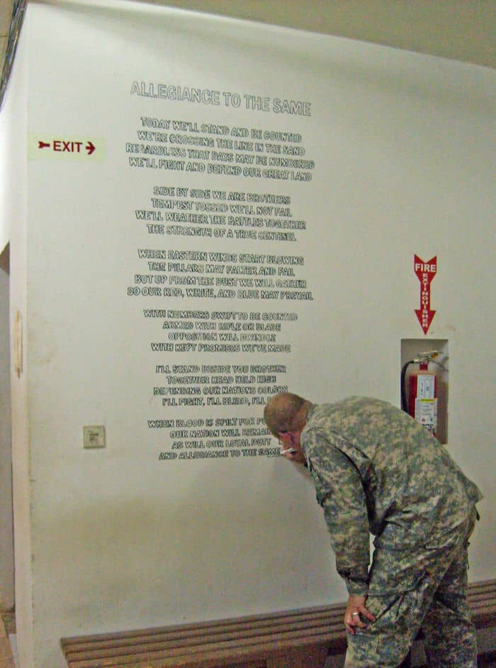 Spc. Flint Christensen, a heavy wheel mechanic from Rexburg, Idaho, autographs his poem Allegiance to the Same