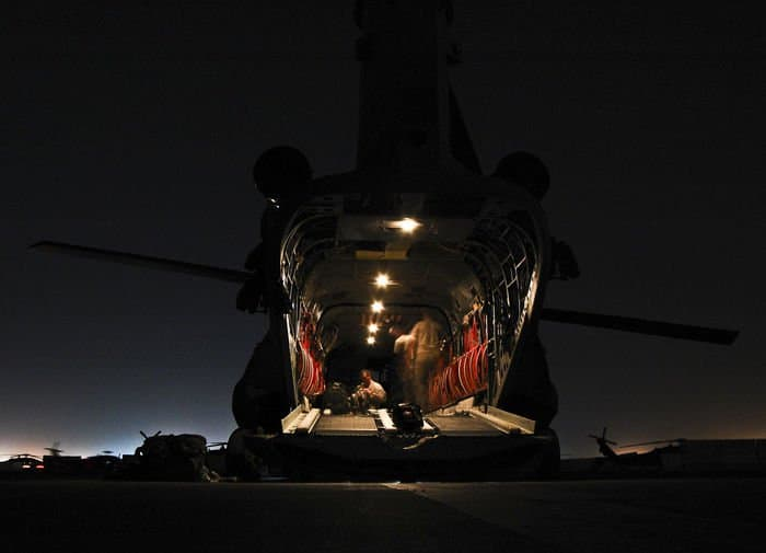 A CH 47F Chinook Improved Cargo helicopter Company B crew prepares the cabin for a late night mission.
