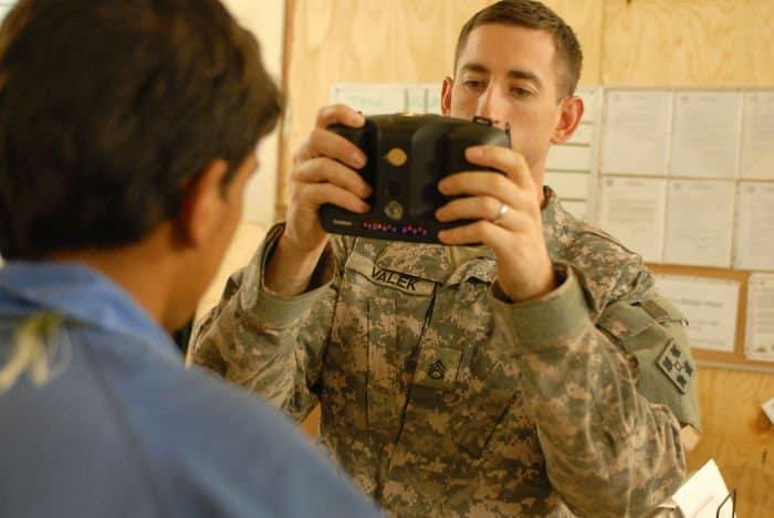 Staff Sgt. Matthew Valek, senior NCOIC of badge operations uses a biometric camera.