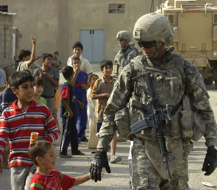 An Iraqi child runs to take the hand of Spc. Chris Jackson, a Washington infantryman. Jackson is a favorite of the children.