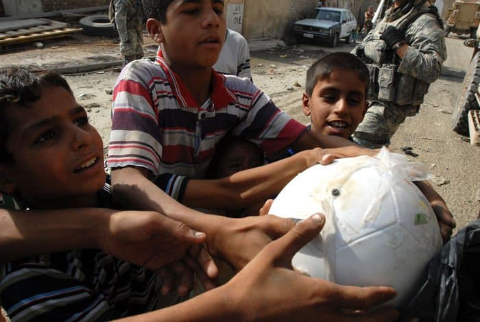Iraqi children jostle for a soccer ball being handed out by Spc. Chris Jackson.