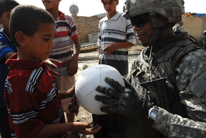 Spc. Chris Jackson hands a soccer ball to a local child of an impoverished Sadr City district neighborhood of Baghdad.