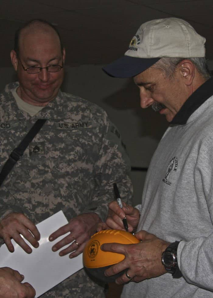 Country music singer Aaron Tippin autographs a football for Staff Sgt. Michael Hood