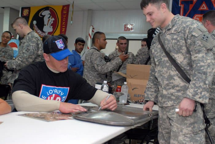 World Wrestling Entertainment Superstar John Cena signs a metal chair for 1st Lt. George Rolston, a Conrad, Iowa, native, at FOB War Eagle