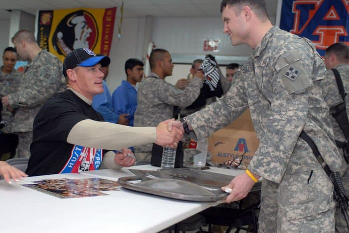 World Wrestling Entertainment Superstar John Cena shakes hands with 1st Lt. George Rolston from Conrad, Iowa, after signing a metal chair at FOB War Eagle
