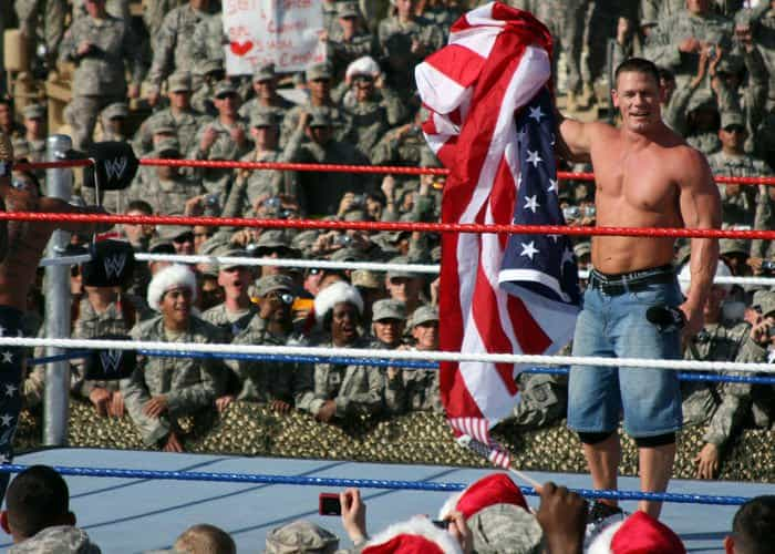 WWE wrestler, John Cena, holds up the US Flag while paying tribute to the troops in Iraq during the Tribute to the Troops Tour in front of Al Faw Palace.