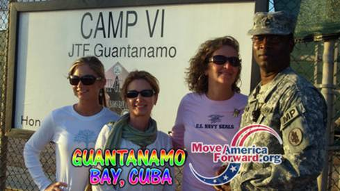 Three visitors with an MP at Gitmo Detention Center.