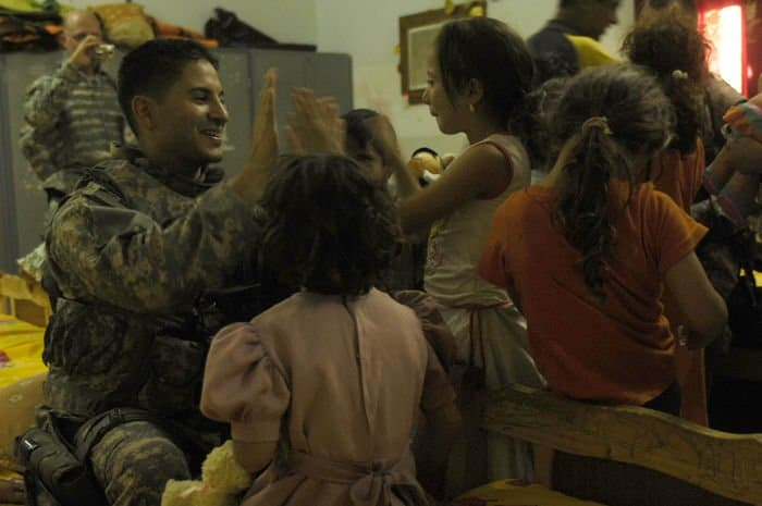 A young Iraqi girl teaches U.S. Army 1st Lt. German Gonzalez, 320th Military Police Company, how to play a game as his unit distributes stuffed animals to Tikrit Orphanage children.