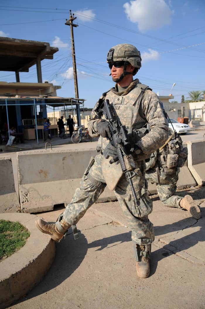 U.S. Army Spc. Daniel Hernandez from the 320th Military Police Company, 728th Military Police Battalion, 18th Military Police Brigade, pulls security during the U.S. Army 1st Armored Division band performance, Operation Iron Tuba, in Balad, Iraq