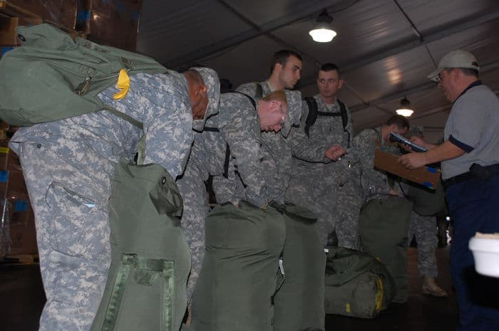 North Carolina Army National Guard Soldiers stand in line, to receive military equipment such as boots, gloves, sunglasses, improved helmets and protective gear.