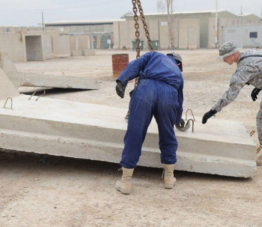 An Iraqi contractor helps Staff Sgt. Russell Walls, take down a barrier wall at Forward Operating Base Rustamiyah in eastern Baghdad.