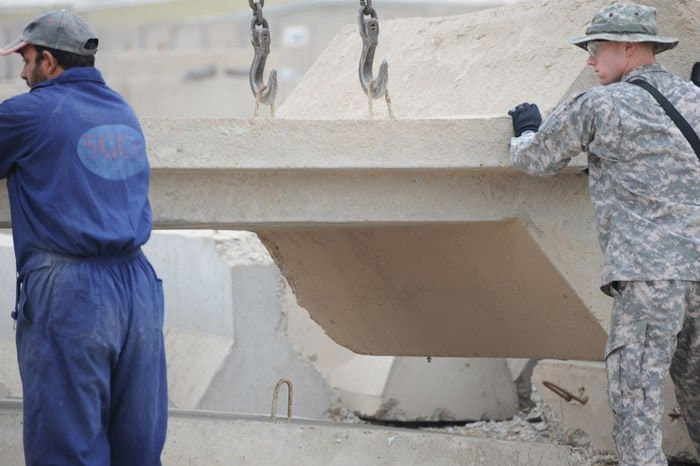 An Iraqi contractor and Staff Sgt. Russell Walls take down a barrier wall at FOB Rustamiyah in preparation for the closure of the base.