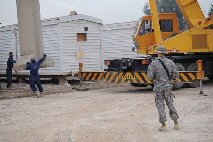 Staff Sgt. Russell Walls oversees Iraqi contractors remove a barrier wall at FOB Rustamiyah.