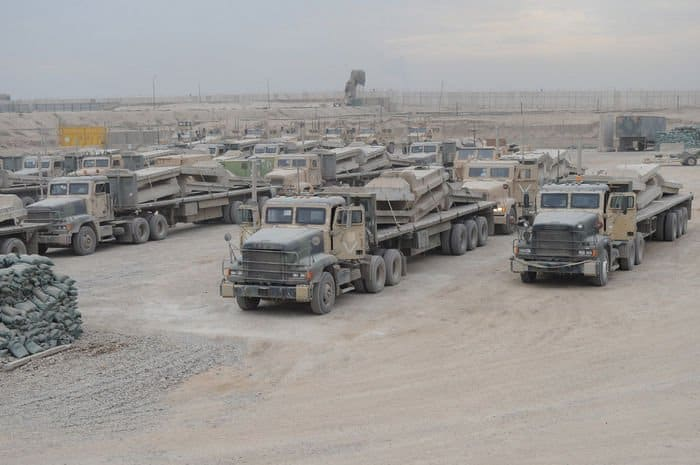 Flat bed trucks loaded with barrier walls prepare to leave FOB Rustamiyah prior to base closure.