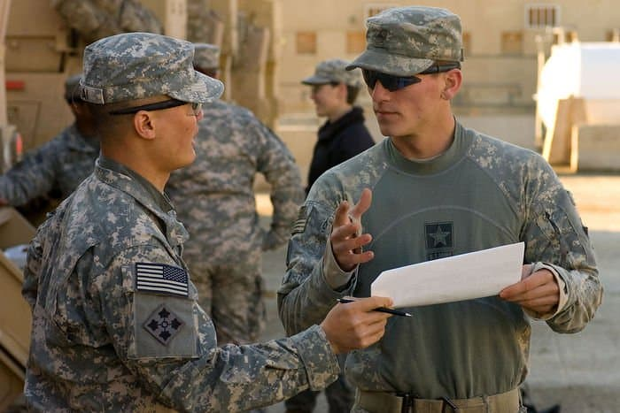 U.S. Army Sgt. Hy Thai, a cavalry scout, and Sgt. Tim Birk, a cable systems installer discuss the operations plan before conducting a convoy in the Rashid district of southern Baghdad.