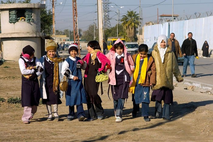 Iraqi students walk to class near Al Rashid Public Library in the Doura community.