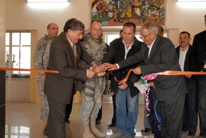 Col John Hort , a Fayetteville, N.C., native, along with local leaders from the Adhamiyah district of Baghdad, cuts the ceremonial ribbon marking the reopening of the Adhamiyah Sports Complex in northeast Baghdad.