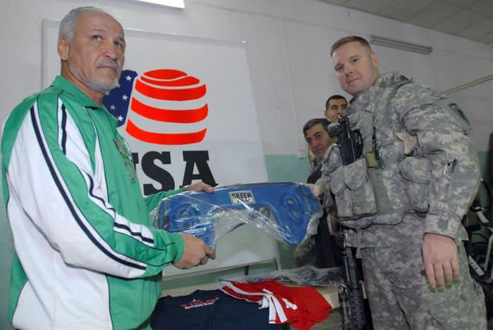 Two time Olympian Farouk Changchun and Capt. William Murphy, a Waltham, Mass., native, pose with gear donated by USA Boxing for the reopening of the Adhamiyah Sports Complex in northeast Baghdad. Changchun represented Iraq in the 1976 and 1980 Olympic Games.