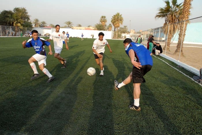 A member of the Adhamiyah soccer team passes the ball to his teammate during a friendly game between Adhamiyah and neighboring Kadhamiyah district, in northeast Baghdad. The game was played as part of the festivities marking the reopening of the Adhamiyah Sports Complex.