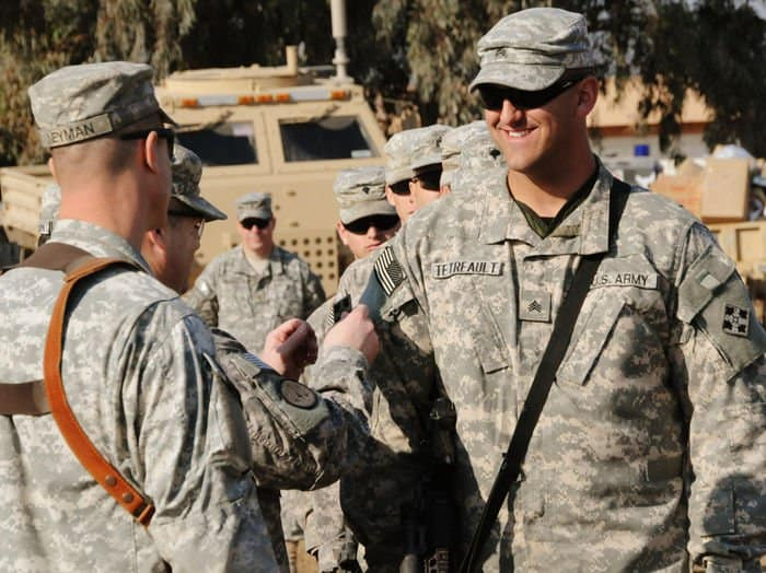 Sgt. Chris Tetreault, mortarman, Troop C, 1 10 Cav. Regt., receives a combat patch from Col. Butch Kievenaar, commander, 2nd BCT, 4th Inf. Div., during a ceremony at PB Mahawil in Babil Province.