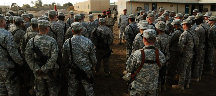 Soldiers from Troop C, 1 10 Cav. Regt., listen to Kievenaar during a combat patch ceremony at PB Mahawil in Babil Province.