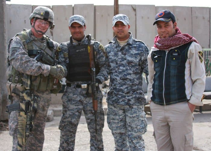 Capt. Chris Carbone, civil affairs team leader and platoon leader for the Enabler Platoon, poses with Iraqi National Police during a dismounted patrol.