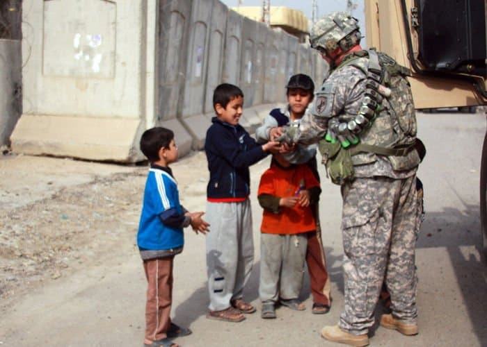 Capt. Chris Carbone, of North Haledon, N.J., gives candy to local Iraqi children during a dismounted patrol.