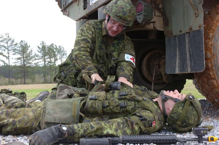 Pvt. Chris Karidogiannis, a medic with the Canadian Forces 51st Area Support Group, administers first aid to a simulated casualty during Counter IED training conducted as part of Operation Noble Guerrier at CSJFTC.