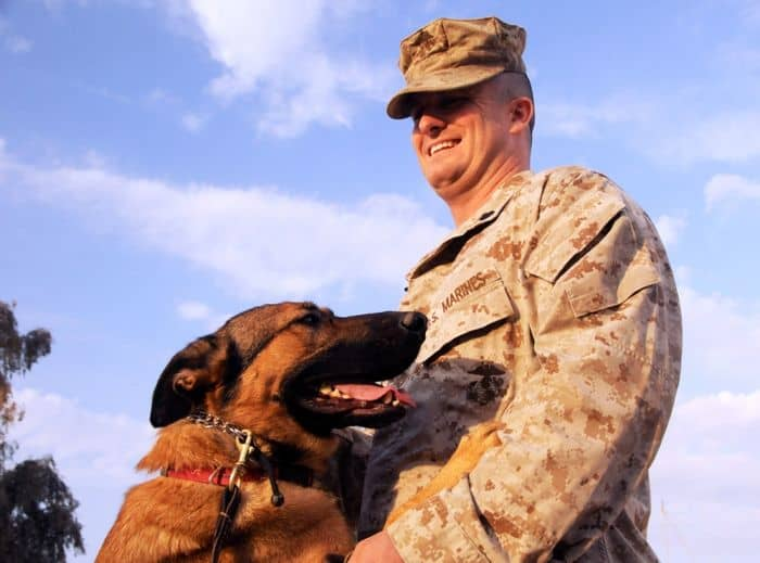 Marine Gunnery Sgt. Lucca, explosive detection dog, and Marine Staff Sgt. Chris Willingham, military working dog handler, Security Battalion, based out of Camp Pendleton, Calif., and attached to STB, 2nd BCT, 4ID, share a hug at Camp Echo.