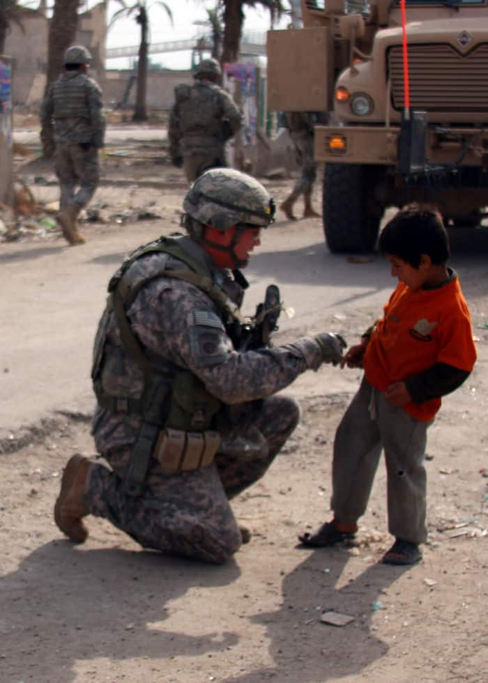 A Soldier with Company C, 1st Battalion, 505th Parachute Infantry Regiment, attached to 1st Brigade Combat Team, 4ID, MND B, visits with a local Iraqi child during a dismounted patrol.