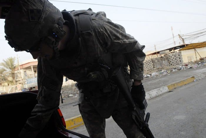 Spc. Cody Cornwall, a cavalry scout from Pocatello, Idaho, assigned to Troop C, 7th Squadron, 10th Cavalry Regiment, 1st Brigade Combat Team, 4ID, MND B, searches the vehicle of an Iraqi citizen caught driving during Iraq Ministry of Interior no driving ban