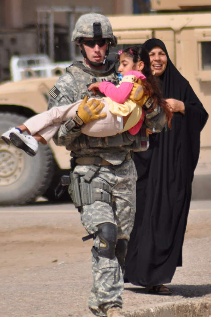 Jesse Stewart, commander of Troop C, 5th Squadron, 73rd Cavalry Regiment, 3BCT, 82nd Airborne Division, carries a disabled Iraqi girl in the Rusafa District of eastern Baghdad. The mother carried her daughter for two miles before almost collapsing near the wheelchair distribution site.