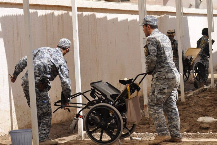 National Police officers assigned to the 3rd Battalion, 8th NP Brigade, 2nd NP Division unload new wheelchairs so they could be donated to disabled Iraqi children in the Rusafa District of eastern Baghdad.