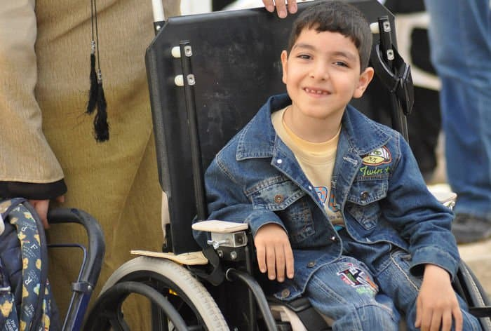 An Iraqi boy smiles after receiving a new wheelchair during a humanitarian event in the Rusafa District of eastern Baghdad. More than 80 wheelchairs were donated by the Wheelchairs for Iraqi Kids. Each wheelchair is valued at ,500 and is adjustable in order to adapt with growing children.