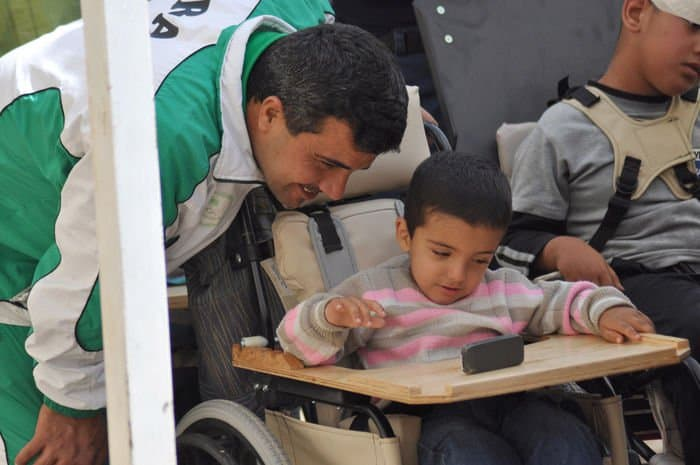 An Iraqi boy and his father share a moment as they look at a cell phone on the new wheelchair in the Rusafa District of eastern Baghdad.