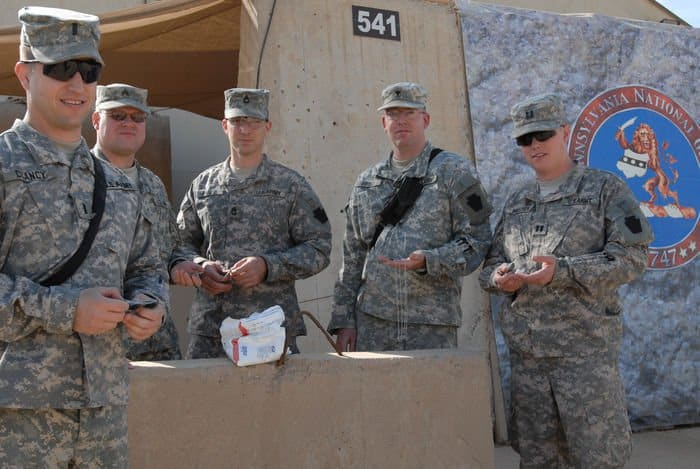 Spc. Michael Frost, of New Castle, Pa., a Soldier with Headquarters and Headquarters Company, 56th Stryker Brigade Combat Team, 28th Infantry Division, began distributing a bag of Dog Tags for Kids keepsakes to Soldiers working in the 56th SBCT headquarters area.